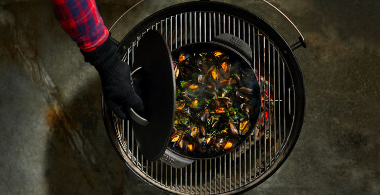 Lifted lid on a pot of grilled muscles on a Weber charcoal grill - Weber gas and charcoal grills